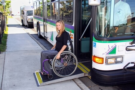 Woman in wheelchair easily accessing the bus